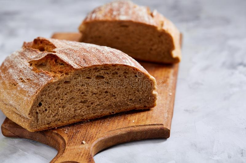 Fresh rye bread loaf on a wooden chopping board over white textured background, shallow depth of field royalty free stock image