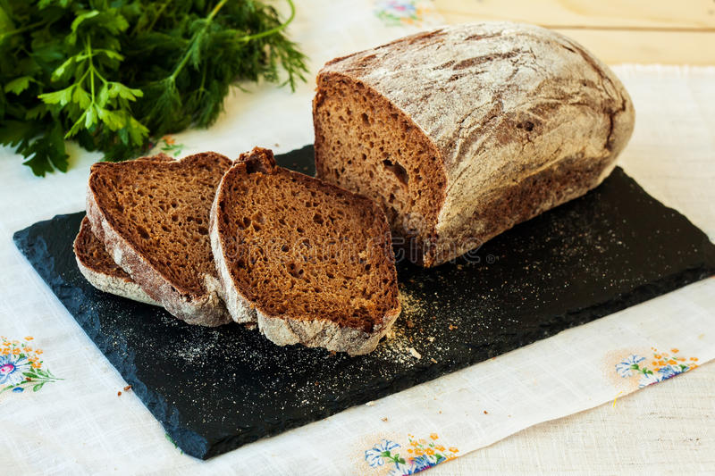 Fresh rye bread on slate plate. Selective focus stock images