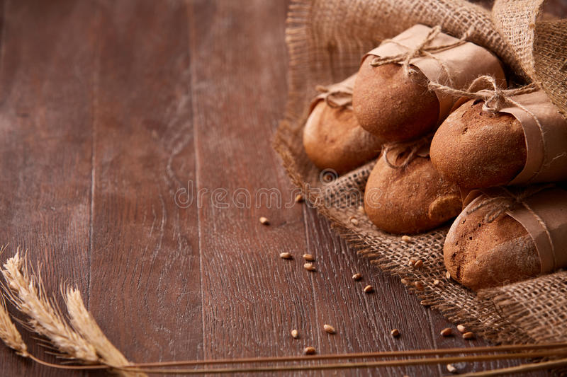 Fresh rye bread on the wooden table, wheat, paper bags, ears of wheat, rope and burlap royalty free stock photo