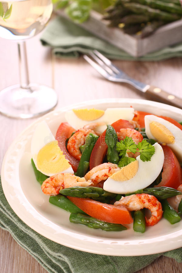 Fresh salad with asparagus, eggs, shrimp and tomatoes.  royalty free stock images