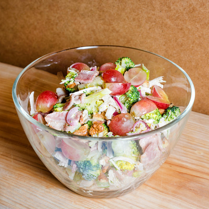 Fresh salad with bacon, grapes, walnuts, greens and herbs and olive oil in transparent glass salad-bowl. Portion of salad on the b stock images