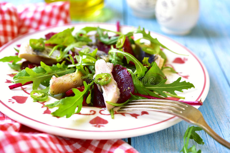 Fresh salad from beetroot,herring,arugula and chard leaves. Fresh salad from beetroot,herring,arugula and chard leaves on a blue wooden table stock photography