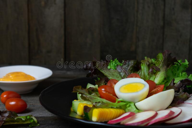 Fresh salad with boiled egg in black dish on wooden table, Tomato and Radish.  royalty free stock photos