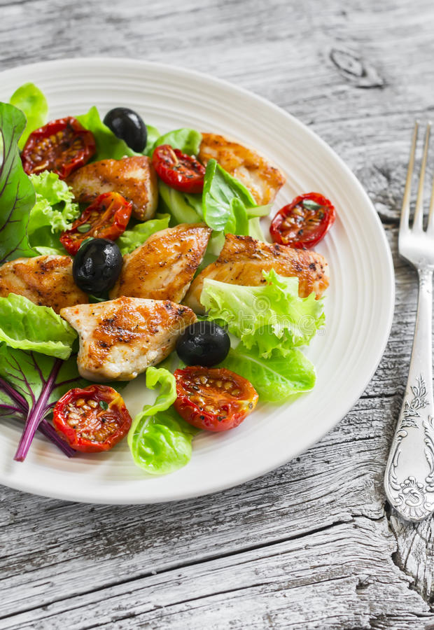 Fresh salad with chicken breast, sun-dried tomatoes, green salad and olives on a white plate stock images