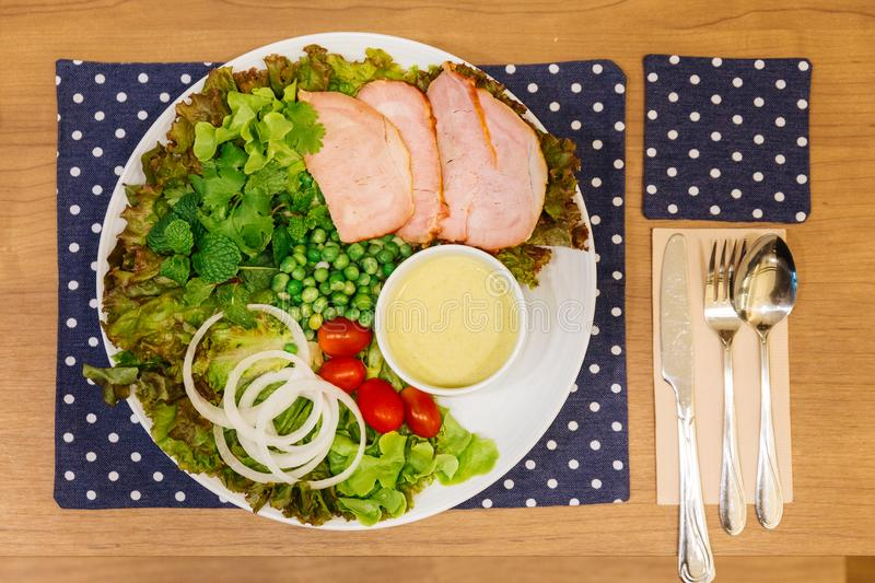 Fresh salad with delicious chicken breast, green oak, lettuce, onion and tomato on blue white dot fabric. Served with mayonnaise stock photo