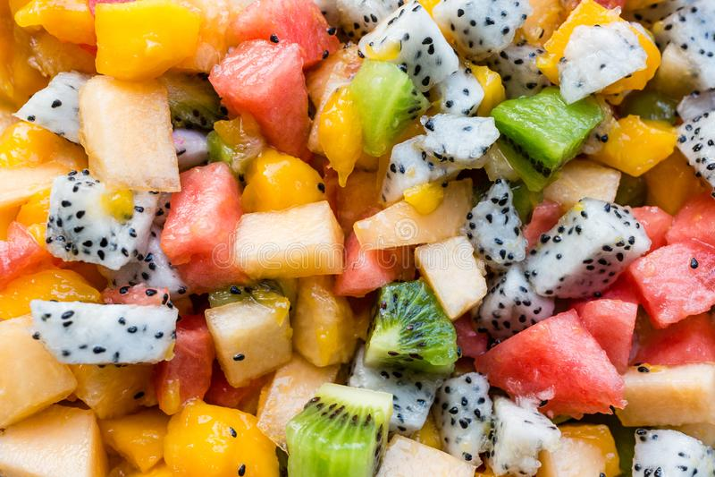 Fresh salad with exotic fruits closeup - papaya, mango, pineapple, passion fruit, dragon fruit, grapes, lichee, kiwi, melon. flat royalty free stock photos