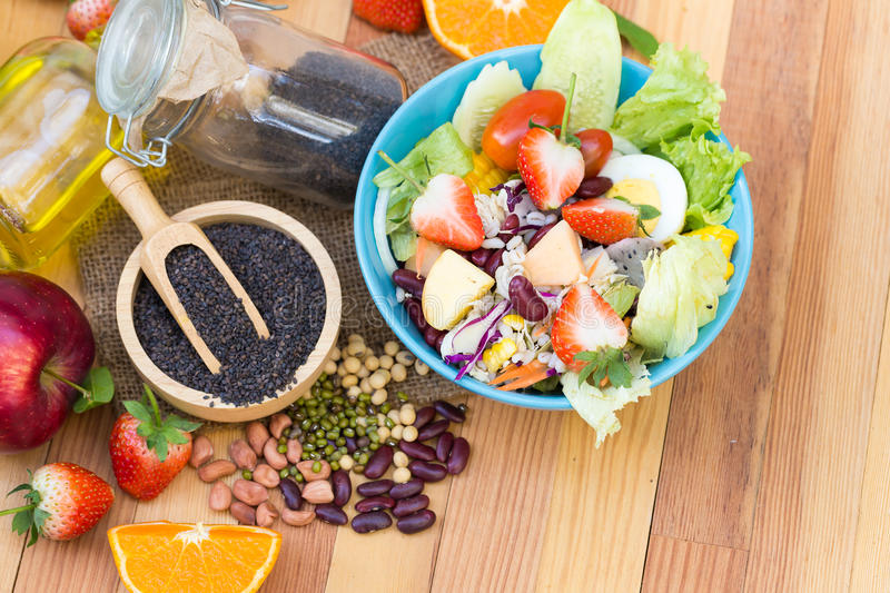 Fresh salad with fruits and Black sesame seeds and oil on woode. N background top view royalty free stock photos