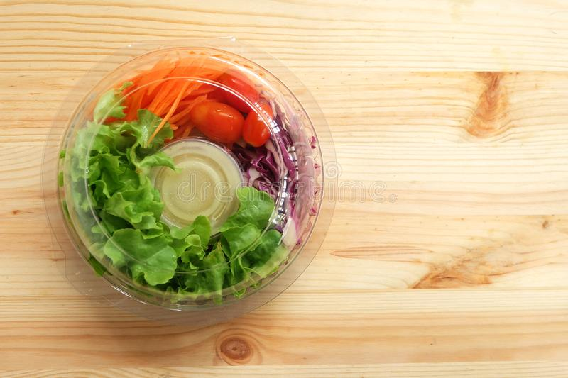 Fresh salad with green oak vegetables, cherry tomatoes, shredded carrots and mayonnaise salad dressing cream in a clear plastic bo. X on wooden floor, Ready to stock photos