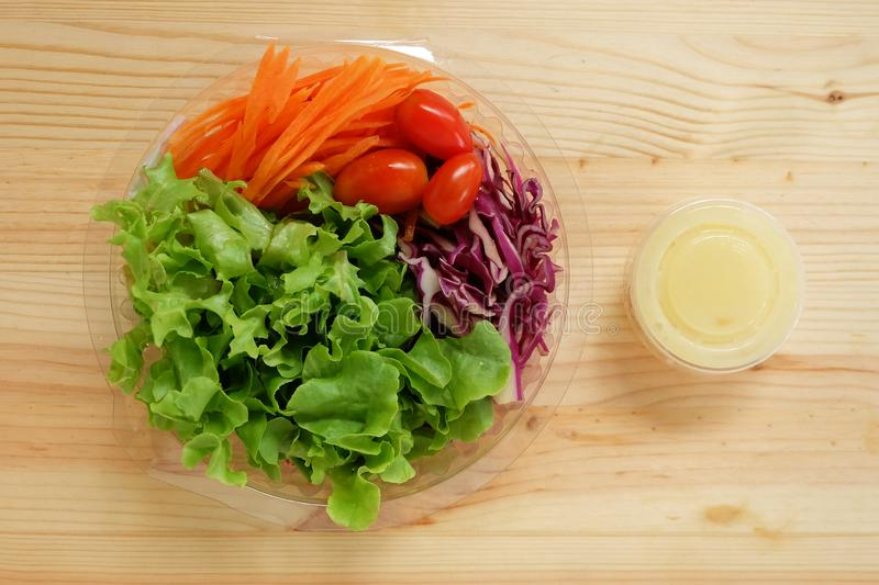 Fresh salad with green oak vegetables, cherry tomatoes, shredded carrots and mayonnaise salad dressing cream in a clear plastic bo. X on wooden floor, Ready to stock image