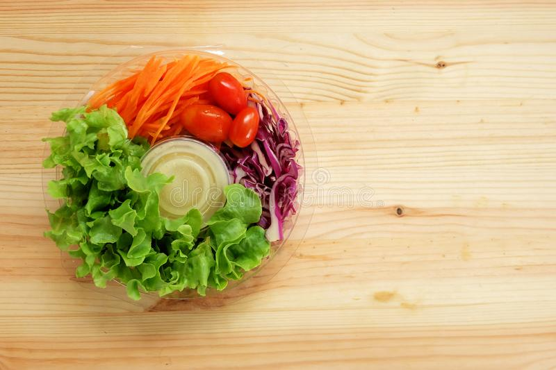 Fresh salad with green oak vegetables, cherry tomatoes, shredded carrots and mayonnaise salad dressing cream in a clear plastic bo. X on wooden floor, Ready to royalty free stock photos