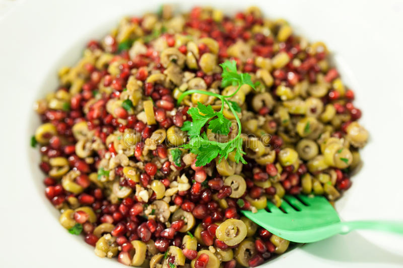 Fresh salad. A fresh healthy salad with olive and pomegranate ready to be served royalty free stock photo