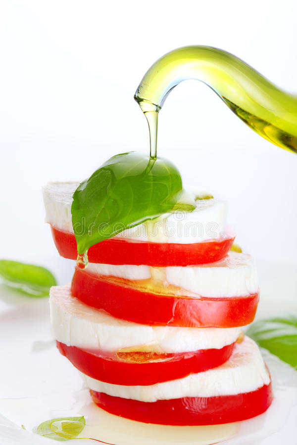 Fresh salad with mozzarella, tomato and basil. With olive oil pouring from bottle stock images