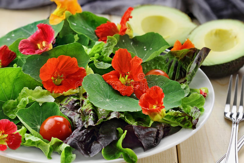 Fresh Salad with Nasturtium Flowers. Cherry tomatoes and avocado. Selective focus with extreme shallow depth of field royalty free stock photos