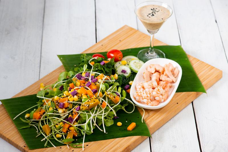 Fresh salad plate with shrimp, salmon, tomato and mixed greens  on wooden background royalty free stock image