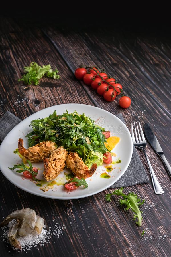 Fresh salad plate with shrimp, tomato, arugula, orange on wooden dark background close up. Healthy food concept in rustic style royalty free stock photography
