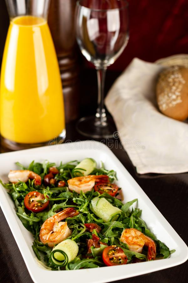 Fresh salad plate with shrimp, tomato and mixed greens arugula, mesclun, mache on wooden background close up. Healthy food. Clean royalty free stock images