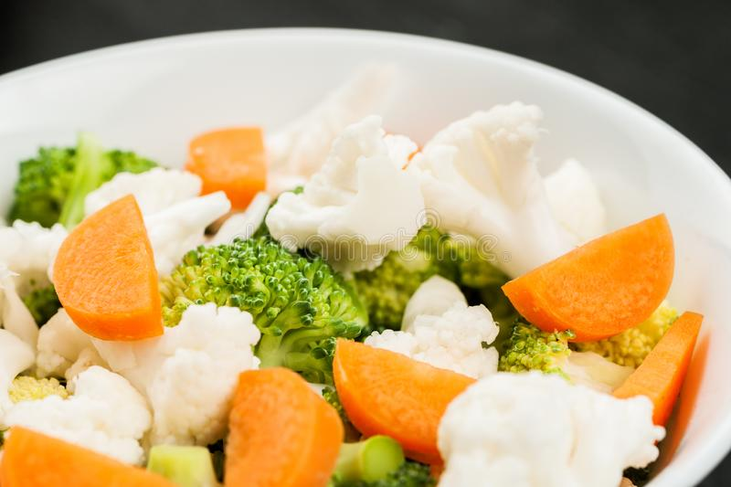 Fresh salad with raw broccoli, cauliflower and carrot in a white dish royalty free stock photography