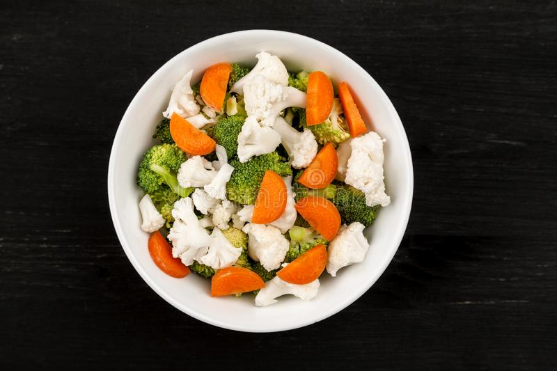 Fresh salad with raw broccoli, cauliflower and carrot in a white dish, top view royalty free stock photography