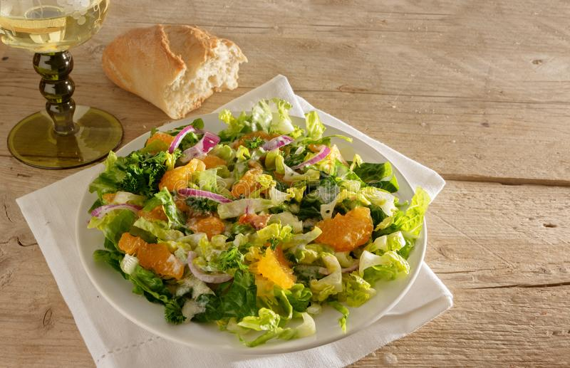 Fresh salad from tangerines and lettuce with red onions on a rustic wooden table, wine and bread, copy space. Selected focus stock photography