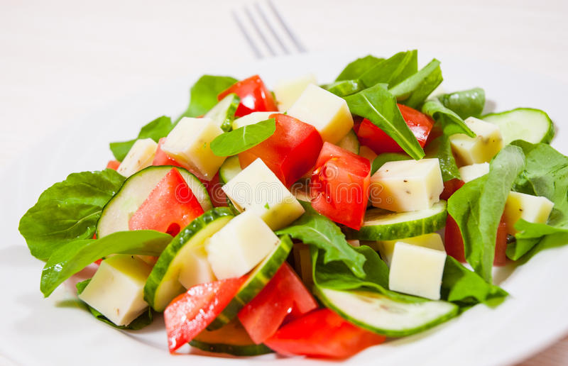 Fresh salad with tomatoes, arugula, cucumber and cheese cubes stock photos
