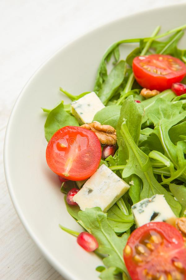 Fresh salad with tomatoes , blue cheese and nutsFresh salad with tomatoes , blue cheese and nuts royalty free stock photo