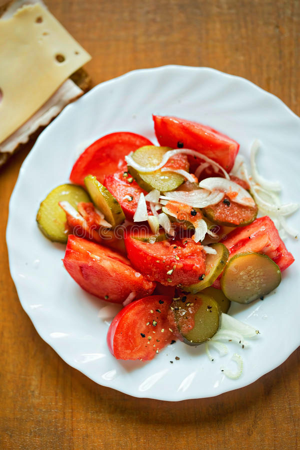 Fresh salad with tomatoes, gherkin and onion, served with ham and cheese sandwich royalty free stock images
