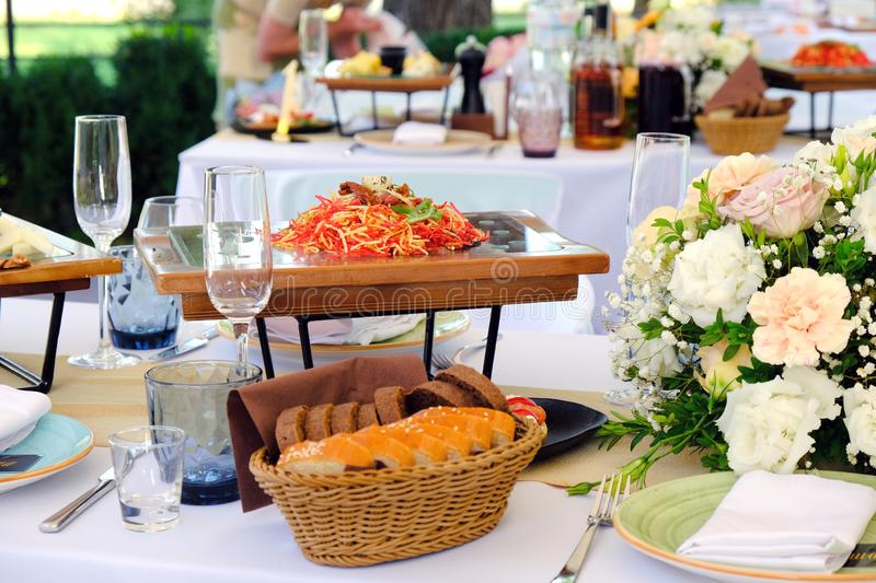 Fresh Salad on a wooden plate on a banquet table decorated with elegant floral bouquet. In luxury restaurant royalty free stock photography