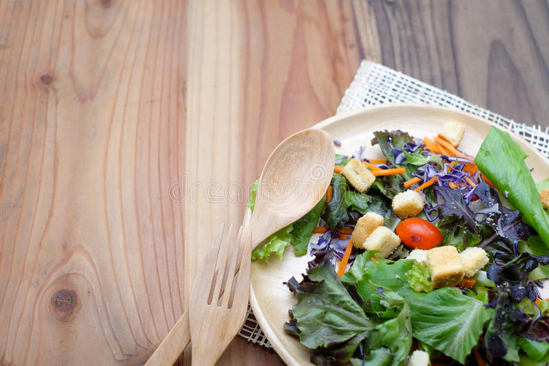 Fresh salad in wooden plate on wood table stock photography