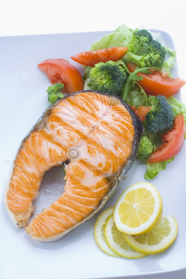 Fresh salmon cooked with salad royalty free stock image