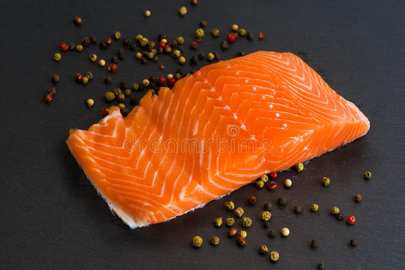 Fresh salmon filet on black cutting board with pepper. Fresh raw salmon filet on black background with pepper stock photo