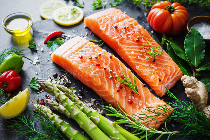 Fresh salmon fillet with aromatic herbs, spices and vegetables stock images
