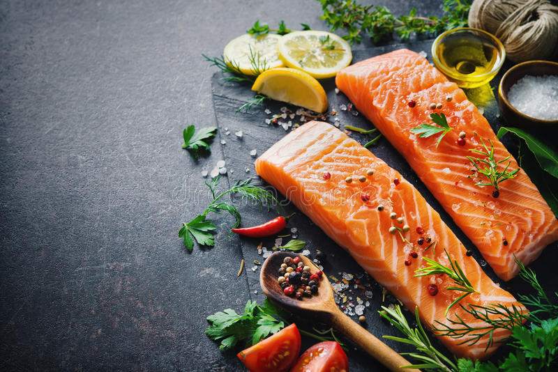 Fresh salmon fillet with aromatic herbs, spices and vegetables royalty free stock images