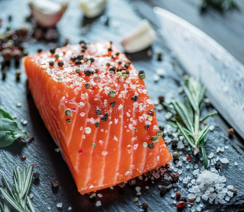 Fresh salmon fillet on black cutting board with herbs and spices royalty free stock image
