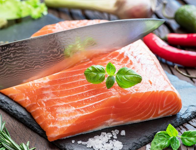 Fresh salmon fillet on black cutting board with herbs and spices royalty free stock photography