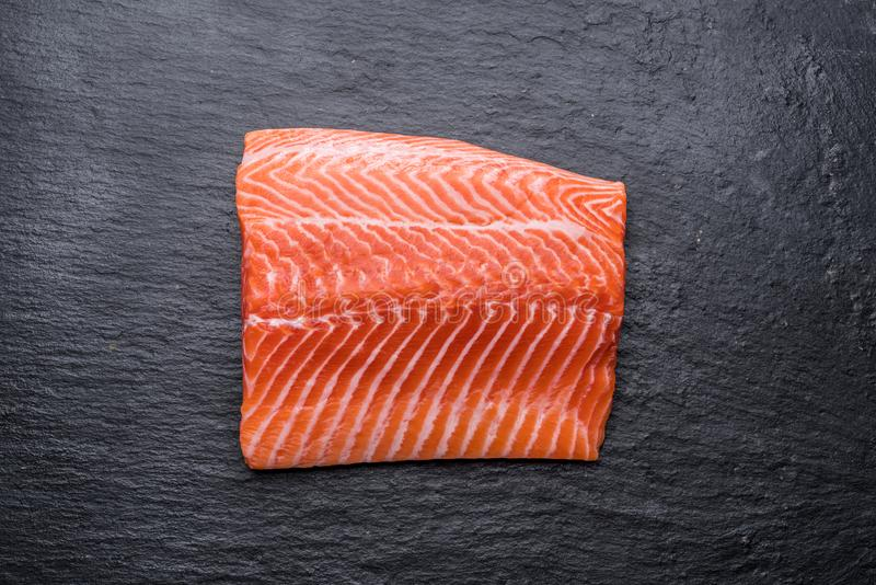 Fresh salmon fillet on black cutting board. Top view.  royalty free stock photo