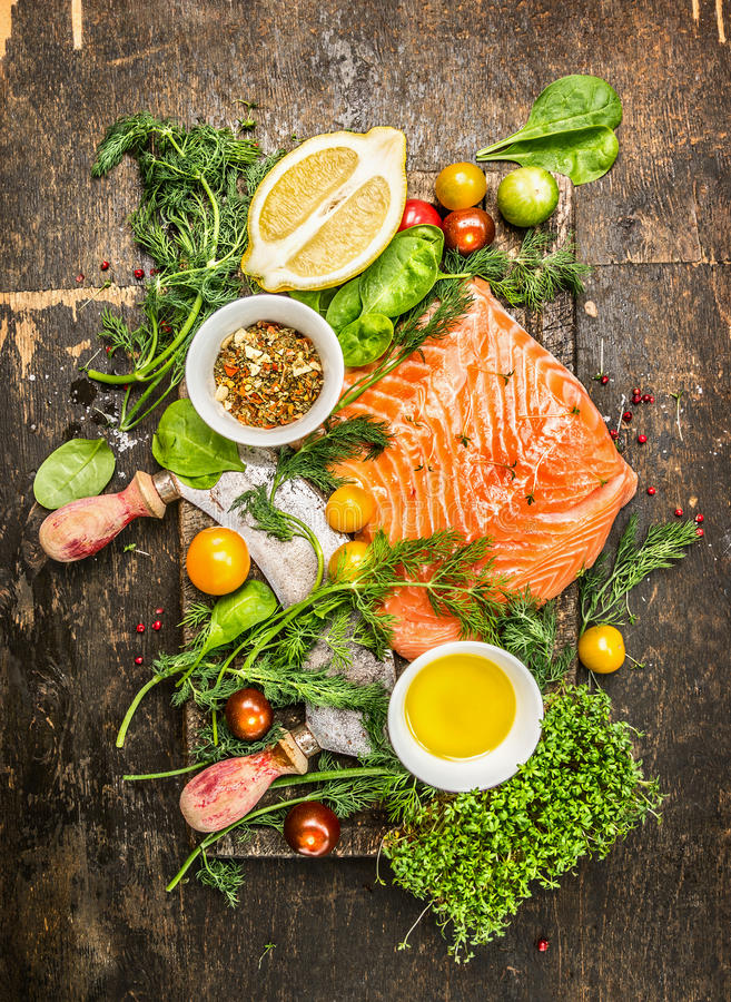 Fresh salmon fillet with fresh healthy herbs,vegetables, oil and spices on rustic wooden background stock photo