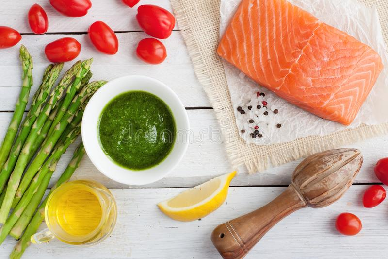 Salmon baked in foil with pesto, tomatoes, asparagus stock images