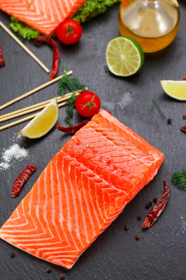 Fresh salmon fillet. Fresh red fish salmon fillet and tomatoes, lime and chili pepper are ready for cooking stock images
