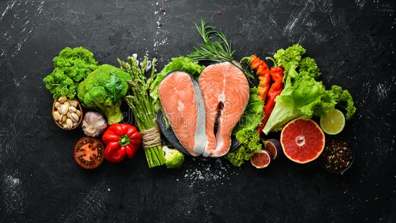 Fresh salmon fillet with vegetables. Healthy eating concept. Top view. Free copy space royalty free stock image