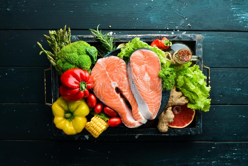 Fresh salmon fillet with vegetables. Healthy eating concept. Top view. Free copy space stock image