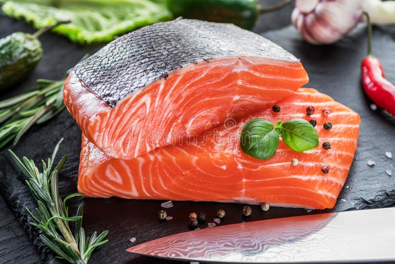 Fresh salmon fillets on black cutting board with herbs and spices royalty free stock photography