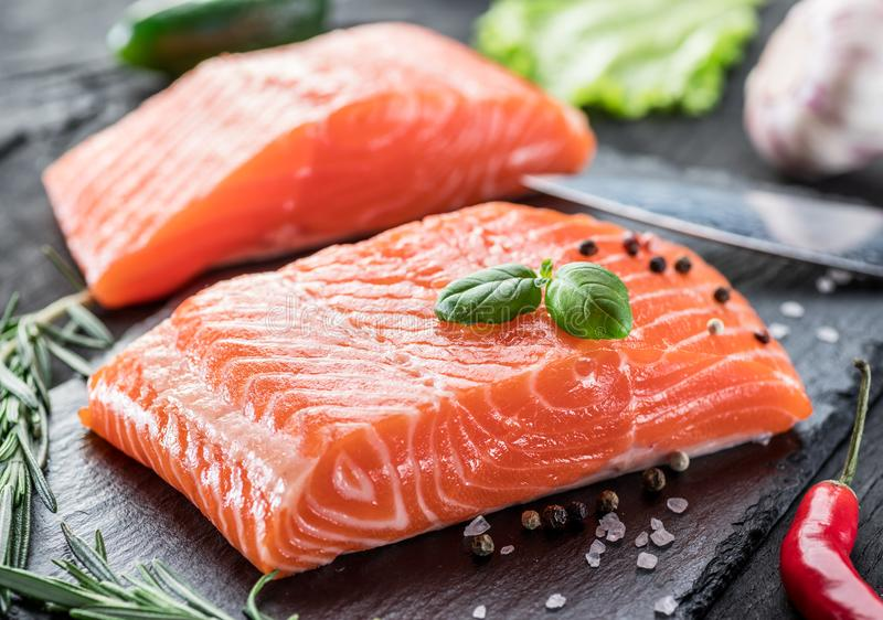 Fresh salmon fillets on black cutting board with herbs and spices royalty free stock photo