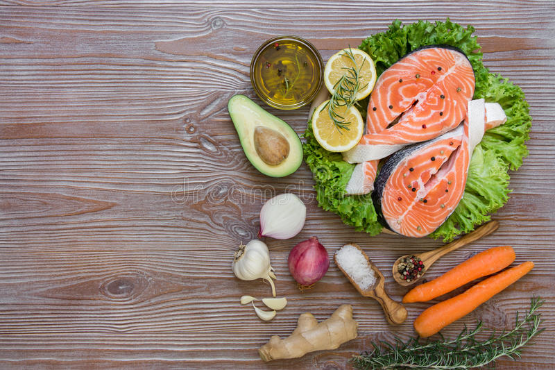 Fresh salmon fillets with seasonal vegetables and spices. Right salmon fillets on lettuce near carrot, avocado, onion, rosemary, lemons, garlic, ginger, spices royalty free stock photos