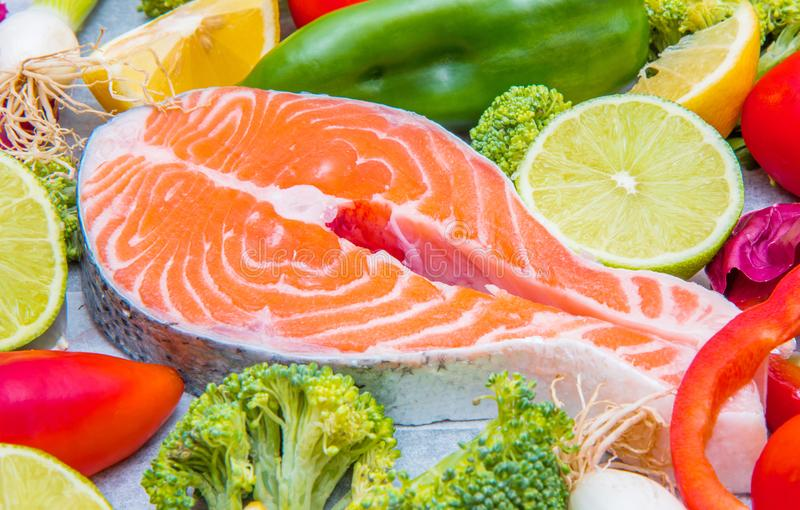 Fresh salmon with fresh and colored vegetables ingredient stock photo