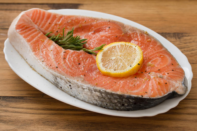 Fresh salmon with lemon on white dish. On brown background stock photography