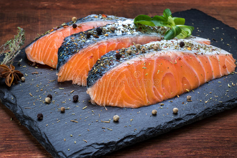 Fresh salmon portions on black tile. royalty free stock photo