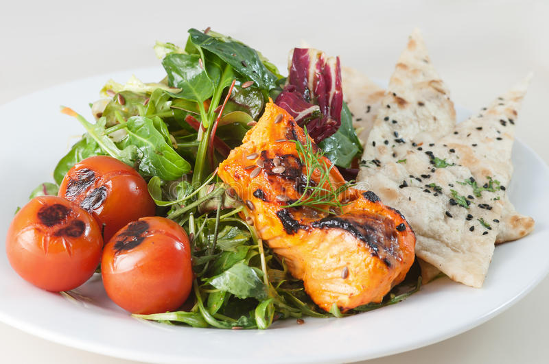 Fresh Salmon salad with chapati. Fresh tandoori salmon salad with green spinach leaves and chapati on white plate royalty free stock image