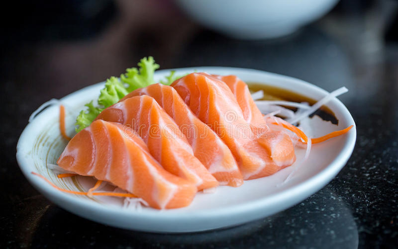 Fresh salmon slice and japanese on dish by lettuce and radish royalty free stock photography