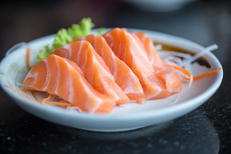Fresh salmon slice and japanese on dish by lettuce and radish stock photography