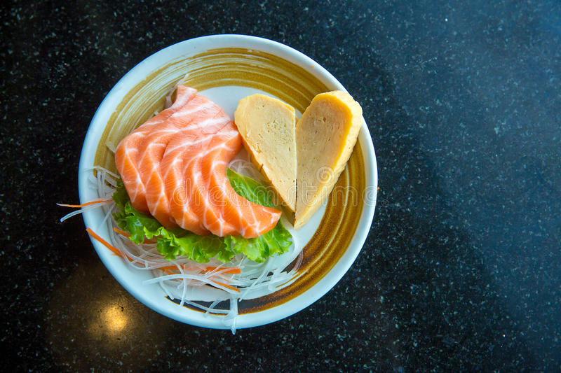 Fresh salmon slice and japanese omelette in heart shaped side dish by lettuce and radish. royalty free stock image